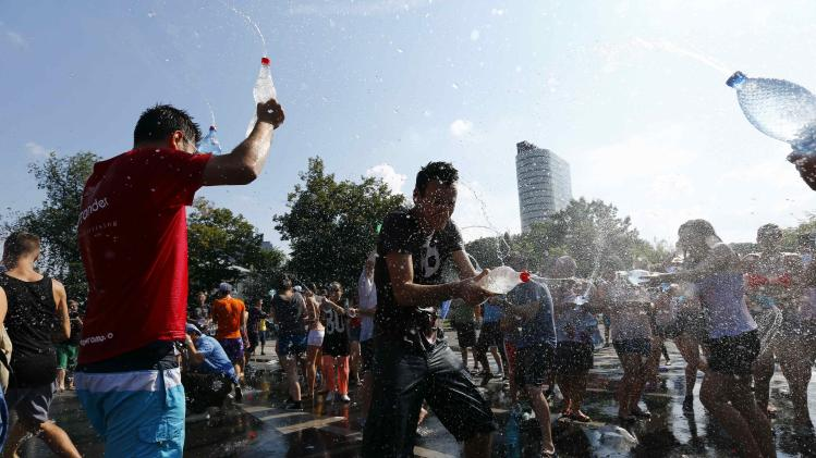 People enjoy a water fight in downtown Bucharest