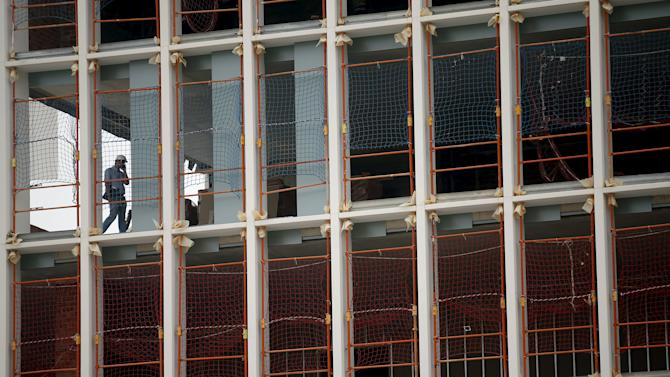 A worker talks by phone in a building under construction in Barcelona