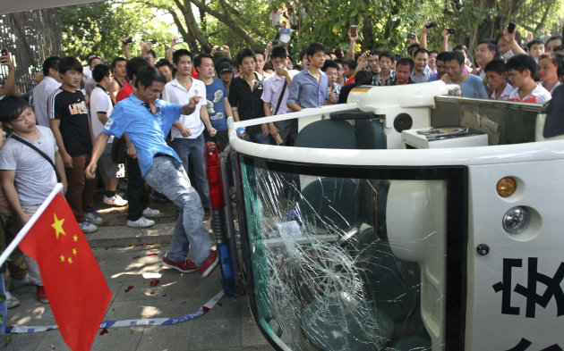 A Chinese demonstrator kicks a broken police vehicle during a protest against Japan in Shenzhen, China Sunday, Sept. 16, 2012. Protesters in China began another day of demonstrations against Japan, af