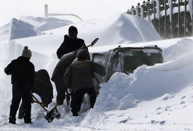 In this photo taken Sunday, March 3, 2013, policemen shovel snow around a vehicle of Kazuyo Miyashita along a road in Nakashibetsu, Hokkaido, northern Japan. Kyodo news service says Miyashita and her 