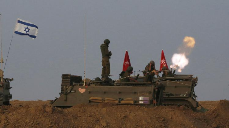 Israeli soldiers stand on an armoured personnel carrier (APC) outside the central Gaza Strip as they fire mortar shell towards Gaza before a ceasefire was due.