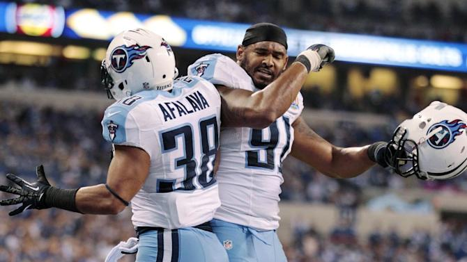 Tennessee Titans' Al Afalava (38) celebrates with Derrick Morgan (91) after Afalava intercepted pass from Indianapolis Colts quarterbac Andrew Luck during the first half of an NFL football game, Sunday, Dec. 9, 2012, in Indianapolis. (AP Photo/Michael Conroy)