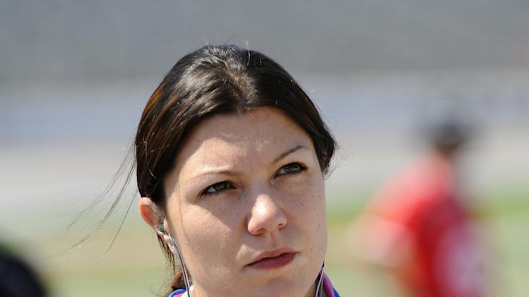 FILE - In this June 8, 2012, file photo, driver Katherine Legge watches before IndyCar Series qualifying at Texas Motor Speedway in Fort Worth, Texas. Legge has threatened legal action over her termination from Dragon Racing on Wednesday, Feb. 13, 2013, one day after the team said Sebastian Saavedra had been hired to drive the No. 6 this IndyCar season. (AP Photo/Ralph Lauer, File)