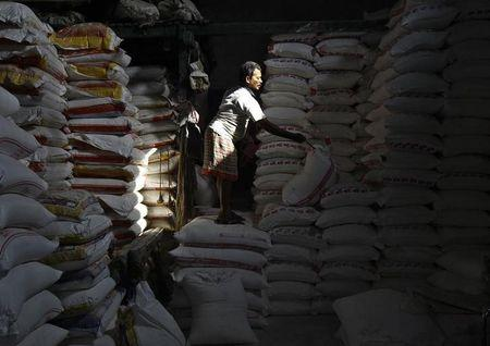 A labourer writes serial number on a sack filled with flour at a wholesale market in Kolkata