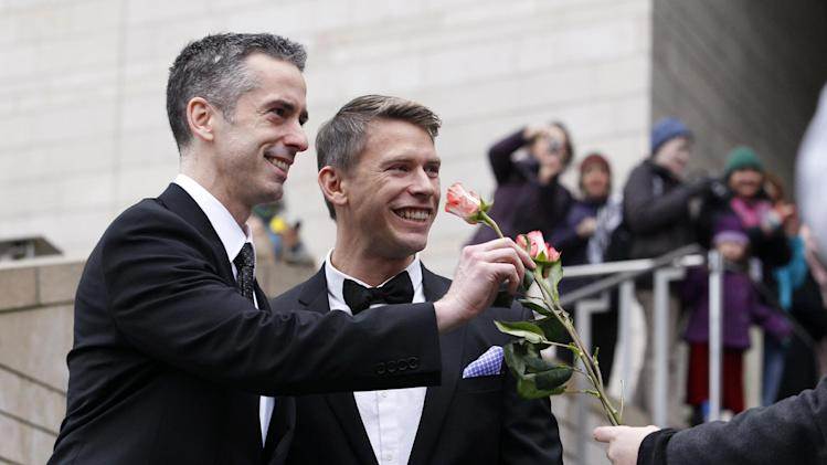 Dan Savage, left, and his husband Terry Miller are handed flowers after their wedding at Seattle City Hall, Sunday, Dec. 9, 2012, in Seattle. Gov. Chris Gregoire signed a voter-approved law legalizing gay marriage Wednesday, Dec. 5 and weddings for gay and lesbian couples began in Washington state on Sunday, following the three-day waiting period after marriage licenses were issued earlier in the week. (AP Photo/Elaine Thompson)