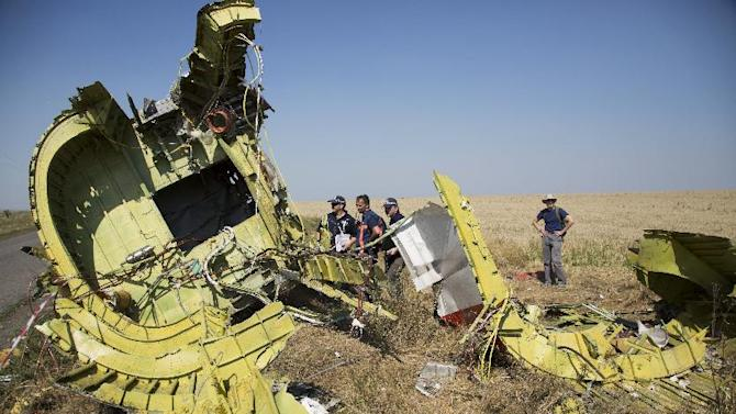 Australian and Dutch investigators examine pieces of the Malaysia Airlines Flight 17 plane crash in the village of Hrabove, Donetsk region, eastern Ukraine Friday, Aug. 1, 2014. The investigators from the Netherlands and Australia plus officials with the Organization for Security and Cooperation in Europe traveled from the rebel-held city of Donetsk in 15 cars and a bus to the crash site outside the village of Hrabove. Then they started setting up a base to work from at a chicken farm. (AP Photo/Dmitry Lovetsky)