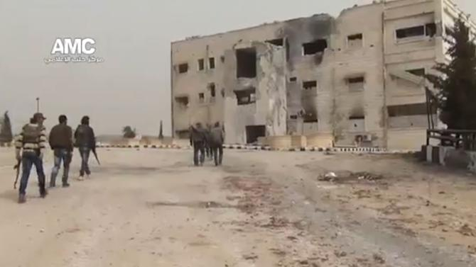 In this Sunday March 3, 2013 image taken from video obtained from the Ugarit News, which has been authenticated based on its contents and other AP reporting, Syrian rebel fighters are seen walking within the police academy complex in Khan al-Asal, in the province of Aleppo, Syria. The Britain-based Syrian Observatory for Human Rights said the rebels seized the police school in Khan al-Asal after entering the sprawling government complex with captured tanks. The Observatory said the battle left at least 120 soldiers and 80 rebels dead. (AP Photo/Ugarit News via AP video)