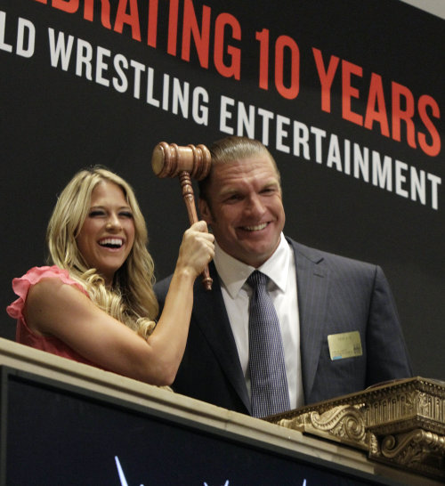 WWE wrestlers Triple H, left, and Kelly Kelly pose photos at a phone post on the floor of the New York Stock Exchange after they rang the opening bell, Wednesday, Oct. 27, 2010, marking 10 years of trading for World Wrestling Entertainment at the NYSE.