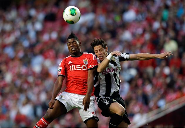 Benfica's Ivan Cavaleiro, left, jumps for the ball with Nacional's Miguel Rodrigues during their Portuguese league soccer match Sunday, Oct. 27, 2013, at Benfica's Luz stadium in Lisbon