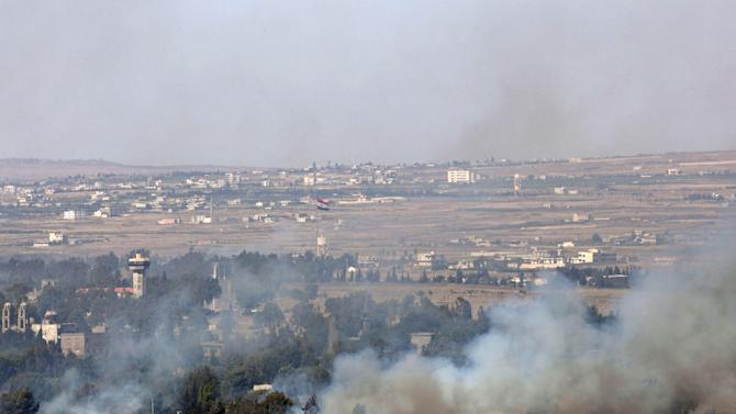 Smoke rises from a fire as a result of fighting in the Syrian village of Quneitra near the border with Israel, as seen from an observatory near the Quneitra crossing, Thursday, June 6, 2013. Syrian rebels on Thursday captured a crossing point along a cease-fire line with Israel in the contested Golan Heights, a development that could deepen Israeli concerns over the growing role of Islamic radicals in the civil war near its northern frontier.(AP Photo/Sebastian Scheiner)