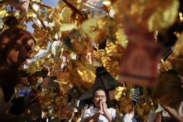 A Buddhist prays under an artificial tree with golden leaves and Thai baht banknotes during a mass alms offering ceremony in Bangkok