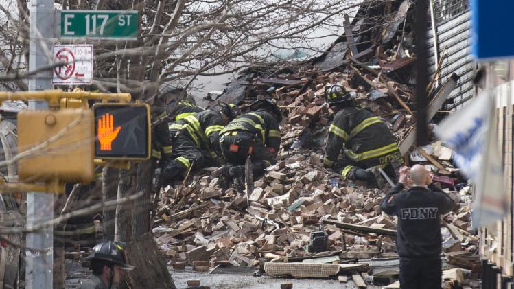 New York City Firefighters dig through rubble at an apparent building explosion fire and collapse in the Harlem section of New York