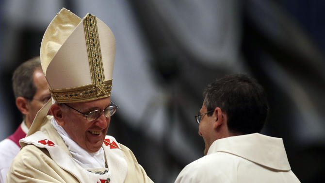 Pope Francis hugs a newly ordained priest during a ceremony in St. Peter's Basilica at the Vatican, Sunday, April 21, 2013. (AP Photo/Gregorio Borgia)