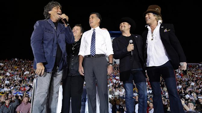 "Republican presidential candidate and former Massachusetts Gov. Mitt Romney sings ""God Bless America"" as he campaigns at the football stadium at Defiance High School in Defiance, Ohio, Thursday, Oct. 25, 2012, with from left to right, Randy Owen, Meat Loaf, John Rich and Big Kenny. (AP Photo/Charles Dharapak)"