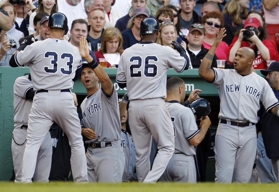 New York Yankees' Nick Swisher (33) celebrates his grand slam that also drove in Eduardo Nunez (26) in the seventh inning of a baseball game against the Boston Red Sox in Boston, Saturday, April 21, 2012. (AP Photo/Michael Dwyer)