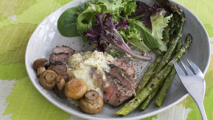 In this image taken on March 11, 2013, grilled lamb steaks with artichoke lemon sauce are shown served on a plate in Concord, N.H. (AP Photo/Matthew Mead)