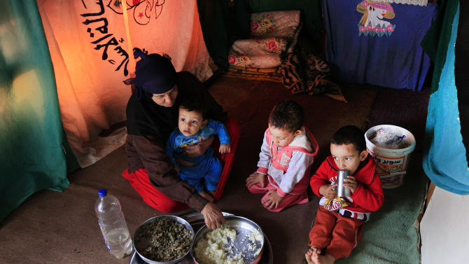 In this on Monday, Feb. 11, 2013 photo, a Syrian woman who fled her home with her family due to fighting between rebels and government forces, feeds her grandchildren inside their tent, in the southern city of Tyre, Lebanon. According to the United Nations refugee agency, there are now more than 265,000 Syrian refugees scattered across Lebanon, straining services in health, education and housing, pushing up prices and causing friction with Lebanese, some of whom resent their presence and blame them for everything from rising crime to the country's notorious traffic. The issue is particularly sensitive given Lebanon's long and complicated history with tens of thousands of Palestinian refugees who fled to Lebanon with Israel's creation in 1948, as well as Syria's long dominance over Lebanese politics. (AP Photo/Mohammed Zaatari)