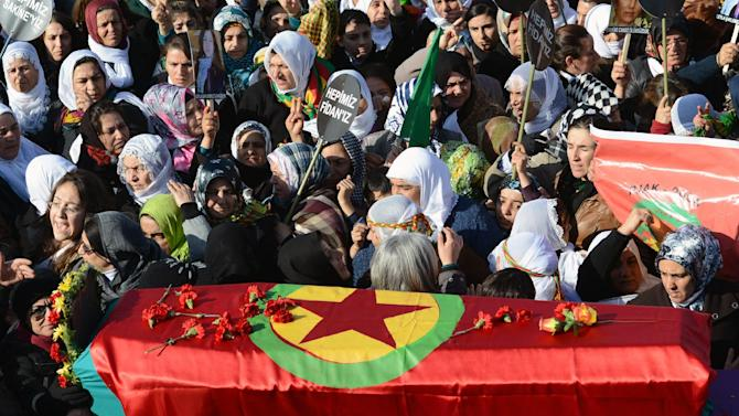 People walk with the coffins, covered with PKK flags, of three Kurdish activists as tens of thousands of people gather for their funeral in Diyarbakir, sourtheastern Turkey, Thursday, Jan. 17, 2013. The three women activists, including a founding member of the outlawed Kurdistan Workers' Party, or PKK, were found shot dead in Paris last week at a time when Turkey is holding peace talks with the rebels' jailed leader. Many believe the killings may be an effort to derail the talks. (AP Photo)