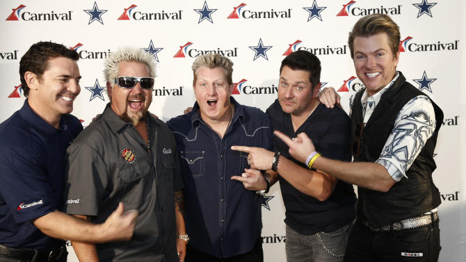 "IMAGE DISTRIBUTED FOR CARNIVAL CRUISE LINES - Mark Tamis, senior vice president of guest operations for Carnival Cruise Lines, left, poses with Chef Guy Fieri, Gary LeVox, Jay DeMarcus and Joe Don Rooney of the Rascal Flatts during Carnival's ""Tailgate Takeover"" before the Dallas Cowboys game against the New York Giants at AT&T Stadium in Arlington, Texas, Oct. 19, 2014. The gameday event is part of the cruise line's multi-year sponsorship of the team.  Fieri, whose namesake Guy's Burger Joints are featured aboard several Carnival ships, tailgated with fans and hosted a Gameday Burger Battle, crowing the best tailgate burger in town. The Rascal Flatts got fans ready with an exclusive pre-game concert and will also perform as part of the Carnival LIVE shipboard concert series next year. Carnival will bring a third year-round ship, Carnival Freedom, to Galveston in February 2015. (Jim Cowsert/AP Images for Carnival Cruise Lines)"