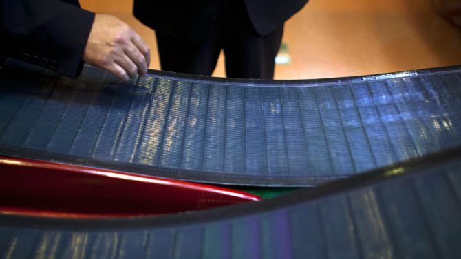 Company executives look at thin-film solar panels developed by MiaSole before a press conference held at the headquarters of Hanergy Group in Beijing, China, Wednesday, Jan. 9, 2013. Hanergy Group, the Chinese company that bought MiaSole, a California producer of thin-film solar panels, said it can make a success of the emerging technology where others have suffered huge losses. (AP Photo/Alexander F. Yuan)