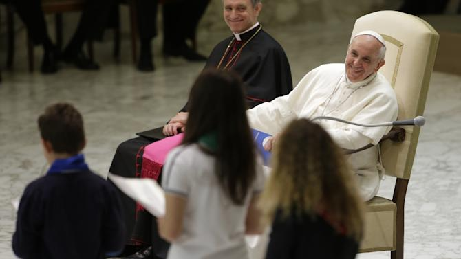 Pope Francis smiles he listens to children reading out their message during an audience with students of Jesuit schools and institutions in Italy and Albania, at the Vatican, Friday, June 8, 2013. Francis is the first pope from the Jesuit order, which is known for its missionary zeal. (AP Photo/Andrew Medichini)