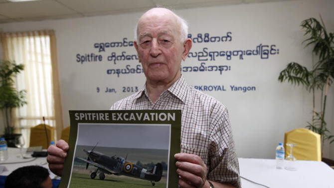 Stanely Coombe, an eye witness of World War II Spitfire aircraft, shows a photo of spitfire aircraft during a press conference at Park Royal hotel Wednesday, Jan.9, 2013, in Yangon, Myanmar. A search team led by a British aviation enthusiast arrived in Myanmar on Sunday to begin a dig they hope will unearth dozens of rare British Spitfire fighter planes said to have been buried in the Southeast Asian country at the end of World War II. (AP Photo/Khin Maung Win)
