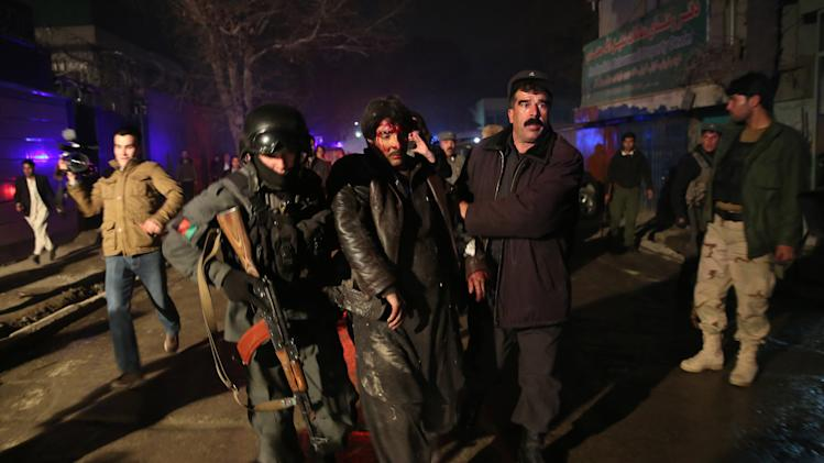 Afghan security forces assist an injured man at the site of an explosion in Kabul, Afghanistan, Friday, Jan. 17, 2014. Afghan police said a suicide bomber attacked a Kabul restaurant popular with foreigners, officials. (AP Photo/Massoud Hossaini)
