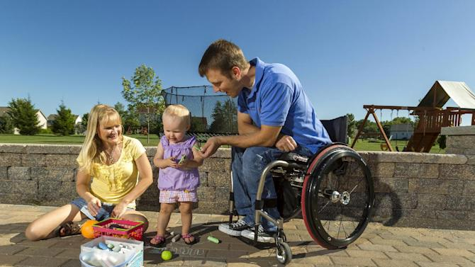 In this photo taken Aug. 6, 2012, Brenda and Chuck Isaacson play in their back yard with their 16-month old daughter, in Sun Prairie, Wis. A bill being considered in the Senate would expand the VA's medical benefits package so other veterans, and their spouses or surrogates, don't have to bear the same expense. The department currently covers a range of medical treatment for veterans, including some infertility care, but the legislation would authorize the VA to cover the cost of IVF and to pay for procedures now covered for some critically injured active-duty soldiers. (AP Photo/Andy Manis)
