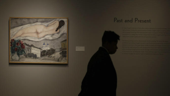 """In this photo taken Wednesday, Feb. 13, 2013, guard stands by the 1933 painting """"Nude Above Vitebsk,"""" by artist Marc Chagall included in the """"Chagall: Beyond Color,"""" exhibit during a preview at the Dallas Museum of Art Wednesday, Feb. 13, 2013, in Dallas. This will be the only U.S. venue to host the exhibit that opens to the public on Sunday. (AP Photo/LM Otero)"""