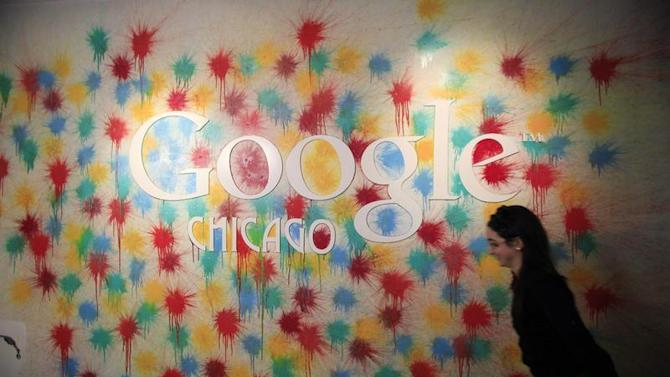 A woman walks past the Google Chicago headquarters logo in Chicago