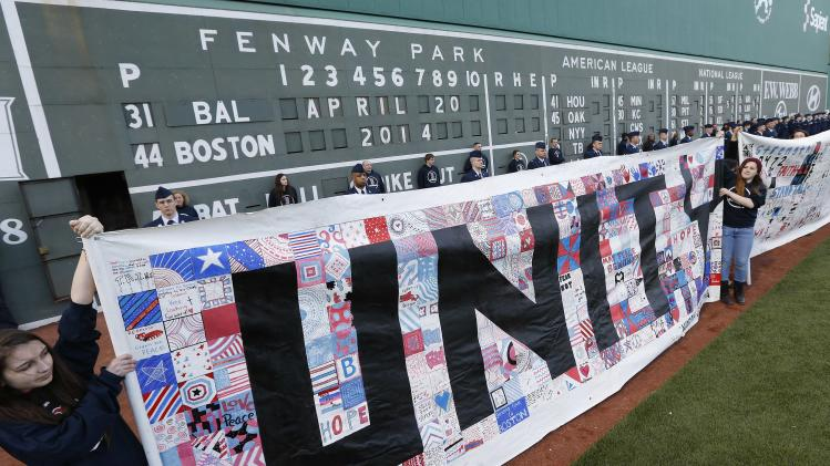 People hold banners in front of the scoreboard at Fenway Park during ceremonies to commemorate the one-year anniversary of the Boston Marathon bombings before a baseball game between the Boston Red Sox and the Baltimore Orioles in Boston, Sunday, April 20, 2014. (AP Photo/Michael Dwyer)
