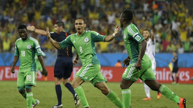 Nigeria's Peter Odemwingie, centre, celebrates after scoring his side's opening goal during the group F World Cup soccer match between Nigeria and Bosnia at the Arena Pantanal in Cuiaba, Brazil, Saturday, June 21, 2014. (AP Photo/Kirsty Wigglesworth)