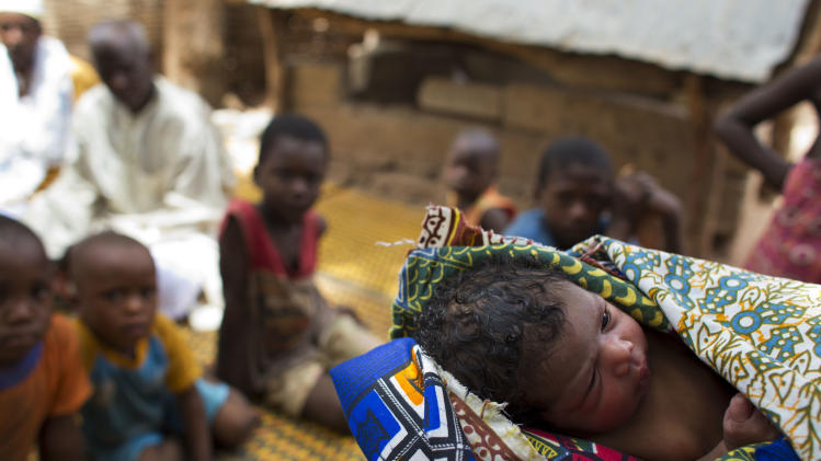 In this May 25, 2012 photo, the as yet unnamed newborn daughter of Fatumata Djau, 32, lies swaddled in fabric amidst grieving family members, at Djau's home in Gabu, Guinea-Bissau. Djau died a day earlier after suffering complications during a solo home birth. She left behind four daughters - including her healthy newborn - a distraught family, and an elderly widower. In the end, the little girl is called Mama Saliu Embalo. It is a boy's name in the Fula language, after a tradition designed to protect children whose mothers have died during childbirth. In Guinea-Bissau, one of the deadliest places in the world to give birth, a woman has a 1 in 19 chance of maternal death, compared to about 1 in 2,100 in the United States. Experts say women are increasingly heading to medical centers when things go awry, but logistical, financial, and cultural barriers are still keeping many pregnant women from seeking help in time. (AP Photo/Rebecca Blackwell)