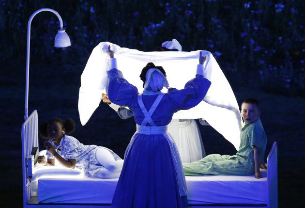 Actors lying on beds meant to represent Britain's National Health Service (NHS) perform during the Opening Ceremony at the 2012 Summer Olympics, Friday, July 27, 2012, in London. (AP Photo/Jae C. Hong)