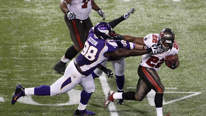 Tampa Bay Buccaneers running back Doug Martin (22) breaks a tackle by Minnesota Vikings defensive tackle Letroy Guion (98) during a 64-yard touchdown reception in the second half of an NFL football game Thursday, Oct. 25, 2012, in Minneapolis. (AP Photo/Andy King)