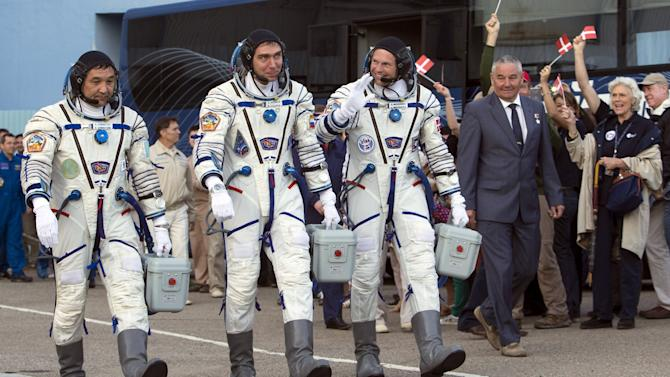 Crew members Aidyn Aimbetov of Kazakhstan, Sergei Volkov of Russia and Andreas Mogensen of Denmark walk after donning space suits at the Baikonur cosmodrome
