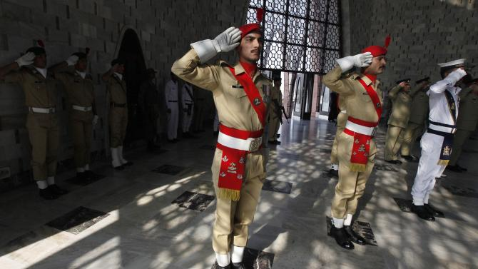 Cadets from Pakistan Military Academy salute during a ceremony to mark 138th birth anniversary of Mohammad Ali Jinnah at his mausoleum in Karachi
