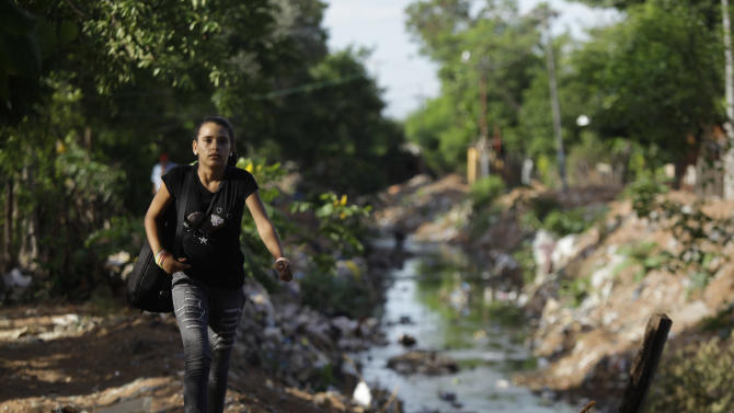 "In this Dec. 11, 2012 photo, Tania Vera, 15, walks from her home alongside a polluted stream to practice with ""The Orchestra of Instruments Recycled From Cateura"" in Cateura, a vast landfill outside Paraguay's capital of Asuncion, Paraguay. I never thought my dreams would become reality,"" said Vera, who lives in a wooden shack by a contaminated stream. Her mother has health problems, her father abandoned them, and her older sister left the orchestra after becoming pregnant. Tania, though, keeps to her goal of becoming a veterinarian as she keeps up with the music. (AP Photo/Jorge Saenz)"