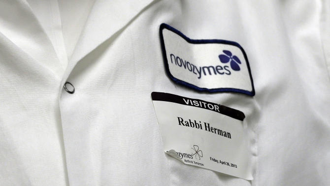 In this Friday, April 26, 2013 photo, Rabbi Pinchas Herman wears his visitor badge as he inspects equipment used for enzyme production for kosher products at Novozymes North America Inc., in Franklinton, N.C. The inspection is an example of how the centuries-old dietary code of observant Jews is adapting to its role as a mark of quality in the global food and drinks industry. (AP Photo/Gerry Broome)