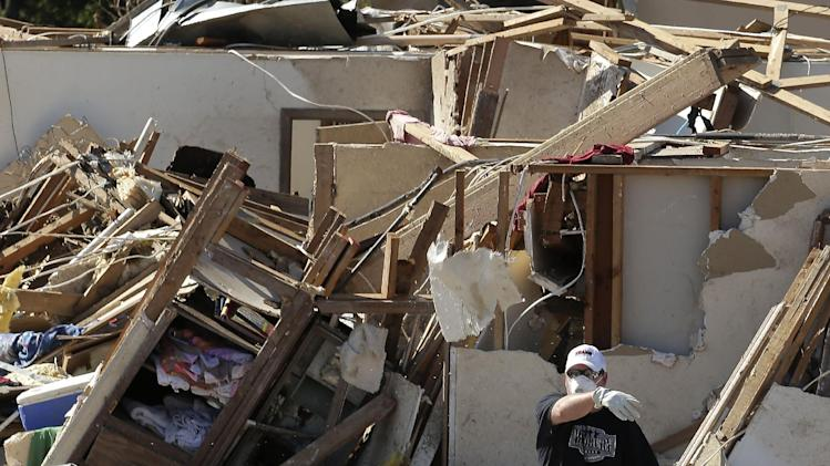 An unidentified man tosses debris as residents sort through their tornado-ravaged homes Wednesday, May 22, 2013, in Moore, Okla. Cleanup continues two days after a huge tornado roared through the Oklahoma City suburb, flattening a wide swath of homes and businesses. (AP Photo/Charlie Riedel)