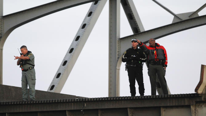 Rescue workers look over the edge where a portion of the Interstate 5 bridge collapsed into the Skagit River in Mount Vernon, Wash., Thursday, May 23, 2013. (AP Photo/Joe Nicholson)