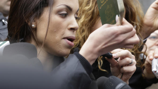 Karima el-Mahroug, also known as Ruby, a Moroccan woman at the center of ex-Premier Silvio Berlusconi's sex-for-hire trial, holds up her passport as she is surrounded by reporters outside Milan's court house, Italy, Thursday, April 4, 2013. The Moroccan woman at the center of ex-Premier Silvio Berlusconi's sex-for-hire trial has denounced what she says is psychological warfare being waged against her by Italian prosecutors. Ruby, read out a lengthy statement Thursday to a gaggle of reporters in front of Milan's courthouse denying she was a prostitute and insisting that prosecutors hear her side of the story. (AP Photo/Luca Bruno)