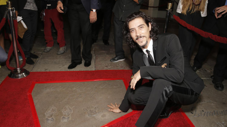 Oscar Jaenada poses at the foot and hand print of Cantinflas at the premiere of Pantelion Film's 'Cantinflas' at TCL Chinese Theatre on Wednesday, August 27, 2014 in Los Angeles. (Photo by Todd Williamson/Invision for Pantelion Films/AP Images)
