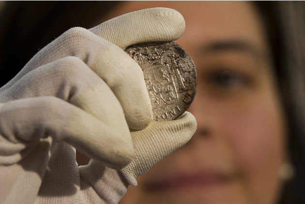 A worker of the ministry holds up for photographers a silver coin from the shipwreck of a 1804 galleon, on its first display to the media at a ministry building, in Madrid, Friday, Nov. 30, 2012. Span