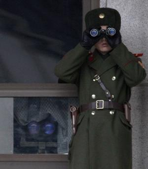 A North Korean soldier looks at the southern side through telescopes at the border village of the Panmunjom, South Korea, Wednesday,  Dec. 8, 2010. The top military leaders from the United States and South Korea were holding talks on the Korean peninsula's security worries on Wednesday, as North Korea was apparently holding its regular firing exercises.(AP Photo/Ahn Young-joon)