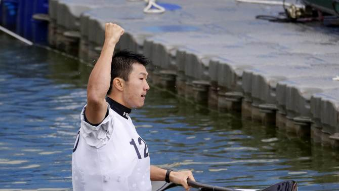 Japan's Kazuya Adachi raises his hand after defeating Taiwan's Pan Hung Ming in the men's kayak single slalom final event at the Hanam Misari Canoe/Kayak Centre, during the 17th Asian Games in Incheon
