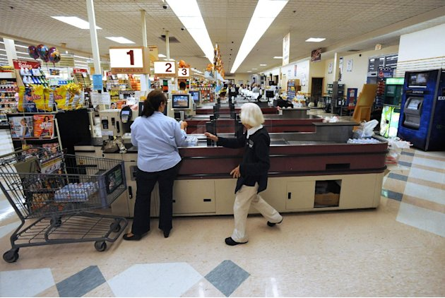 In this Sept. 23, 2011 photo, cashier Joyce Mackie, right, comes to the aid of a customer having a problem at a self-serve checkout station at a Big Y supermarket in Manchester, Conn. A growing  numbe