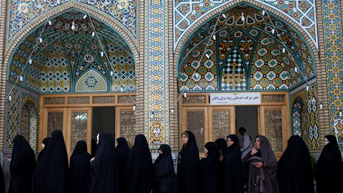 Women wait in line at a polling station to vote during presidential elections in Qom, 125 kilometers (78 miles) south of the capital Tehran, Iran, Friday, June 14, 2013. (AP Photo/Ebrahim Noroozi)