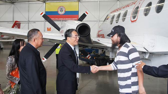 This photo released by China's embassy in Colombia shows China's ambassador to Colombia Wang Xiaoyuan, second from right, shaking hands with an unidentified Chinese former hostage after he was freed along with three others in Bogota, Colombia, Thursday, Nov. 22, 2012. Four Chinese oil workers have been freed in the same southern jungles where the country's largest rebel group kidnapped them 17 months ago, police said Thursday. The four Chinese nationals, three contractors and a translator, were the only foreigners known to still be held by the Revolutionary Armed Forces of Colombia, or FARC. (AP Photo/Chinese Embassy in Colombia)