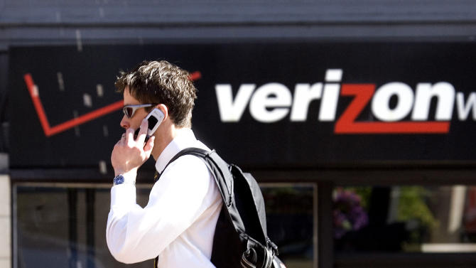 FILE - In this Monday, July 28, 2008, file photo, Eric Roden speaks on his cell phone as he walks past a Verizon store in Portland, Ore. Verizon says, Monday, Sept. 2, 2013, it has agreed to buy Vodafone's stake in Verizon Wireless for $130 billion. (AP Photo/Don Ryan, File)